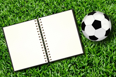 soccer match: Football and blank notebook on Green Grass Stock Photo