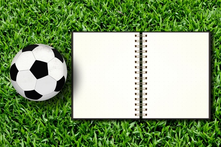 Football and blank notebook on Green Grass Stock Photo