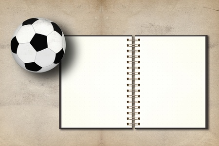Football and blank notebook on grunge vintage background photo
