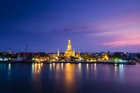 Twilight view of Wat Arun across Chao Phraya River during sunset in Bangkok, Thailand Stock Photo