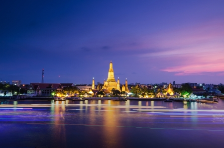 Twilight view of Wat Arun across Chao Phraya River during sunset in Bangkok, Thailand Stock Photo