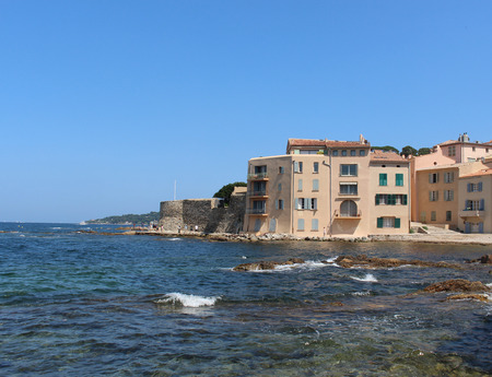 La Ponche Saint-Tropez beach on a sunny summer day. Blue sky, clear water of the Mediterranean Sea and the stone wall of the historic fortress. Saint-Tropez, Provence-Alpes-Côte dAzur, southeastern France.