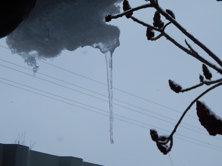 Winter icicles hang from the roof of the building
