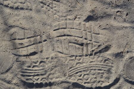 Footprints of shoes on forest sand close-up