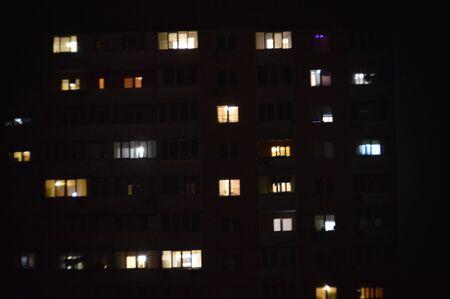 Panorama of night windows of multi-storey buildings in city