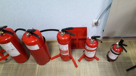 A group of red fire extinguisher cylinders stand on floor