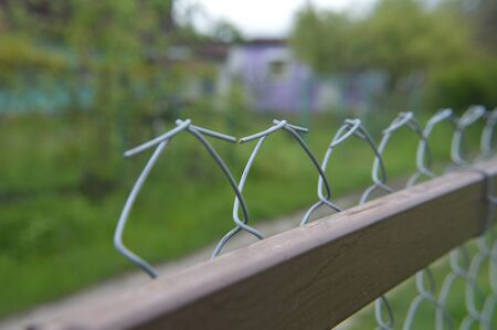 Tensioning and securing a mesh fence with a the metal wire netting