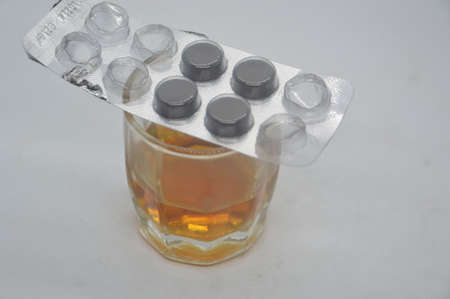 A glass of cognac with medicinal pills on it on a the white background