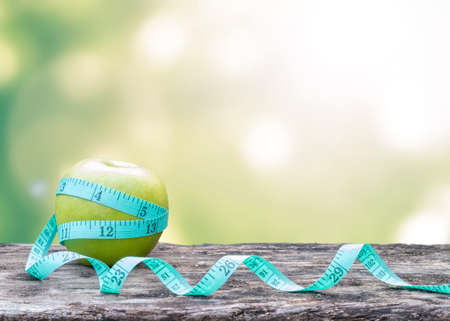 Slim diet, eating habit for healthy living and anti-aging concept with measuring tape wrapping around green apple on old aged wood table background