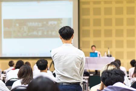 Sesión de preguntas y respuestas del seminario con una vista trasera del participante de pie entre el grupo de audiencia que participa en hacer una pregunta al orador para obtener una respuesta en una conferencia de negocios para emprendedores o una sala de conferencias educativa