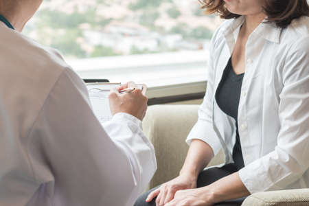 Doctor (obstetrician, gynecologist or psychiatrist) consulting and diagnostic examining woman patient's obstetric - gynecological health in medical clinic or hospital healthcare service center 스톡 콘텐츠