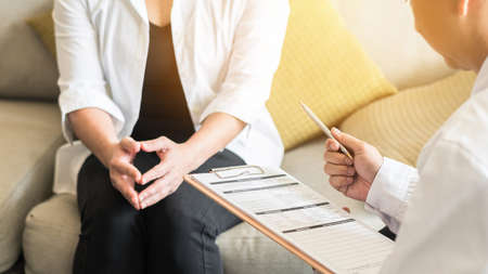 Doctor (gynecologist or psychiatrist) consulting and examining woman patient's health in medical clinic or hospital health service center