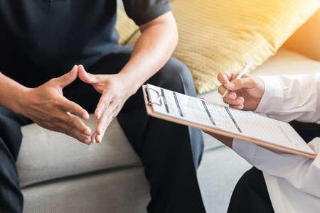 Médico que consulta a un paciente masculino, trabaja en un examen de diagnóstico sobre la enfermedad de salud de los hombres o enfermedad mental y escribe en el documento de información del registro de prescripción en la clínica o en la oficina del hospital
