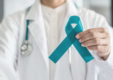Teal awareness ribbon in doctor's hand, symbolic bow color for supporting patient with Ovarian Cancer, PCOS and PTSD Illness