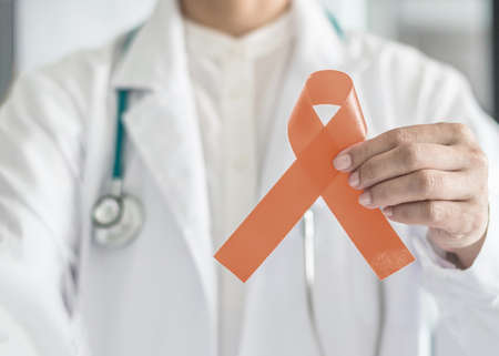 Uterine and Gynecologic Cancer Awareness peach color ribbon (isolated with clipping path) in doctor's hand