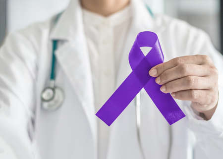 Hodgkins lymphoma and testicular cancer awareness violet ribbon symbolic bow color on doctor's hand support