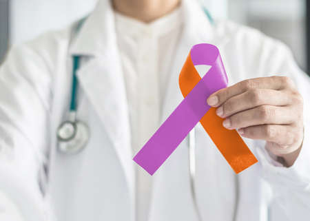 Psoriasis illness and Eczema Dermatitis skin disease awareness campaign concept with orchid purple orange ribbon symbolic bow color on doctors hand support