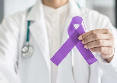 Orchid purple (lavender) ribbon awareness in doctor's hand for  (all kinds cancers), Testicular Cancer awareness, Craniosynostosis, Epilepsy, Hodgkin's lymphoma, National Cancer Prevention Month Stock Photo