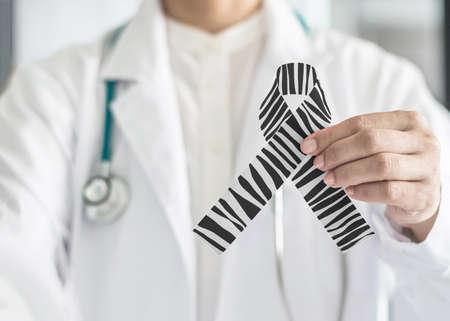 Cinta de concientización sobre el cáncer carcinoide, raya de cebra, patrón blanco y negro, color del arco simbólico en la mano del médico
