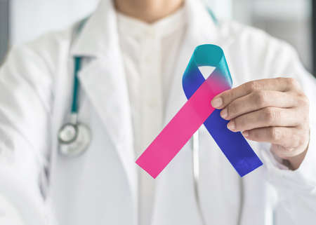 Thyroid cancer awareness ribbon in Teal Pink Blue symbolic bow color in doctor's hand to support patient with tumor illness Фото со стока