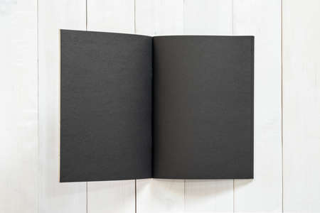 Blank A4 size black book template mock up with open double page placing on creamy white surface wood  table Stock Photo