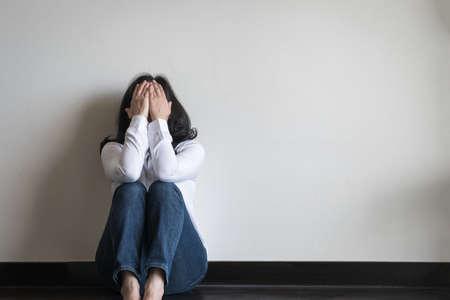 Stressige Frau, die traurig mit emotionaler Depression und Angst auf dem Boden im Wohnzimmer mit weißer Wand sitzt Standard-Bild