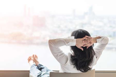 Détente d'un style de vie simple avec une femme d'affaires asiatique qui a un mode de vie sain, reposez-vous facilement dans un hôtel confortable ou un salon à la maison en ayant du temps libre avec la tranquillité d'esprit et l'équilibre de votre santé Banque d'images