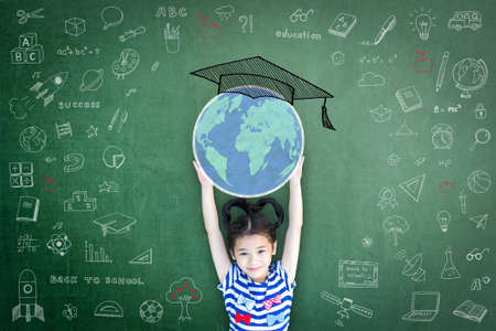 Schulmädchen-Kind, das Weltkugel und Abschlusskappen-Doodle auf grüner Tafel für Kinderbildungskonzept anhebt