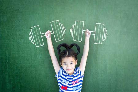 Wzmocnienie koncepcji praw płci kobiety i dziewczyny na międzynarodowy dzień dziewczynki oraz sport dla rozwoju i pokoju ze zdrowym silnym dzieckiem z doodle ćwiczenia hantle na szkolnej tablicy
