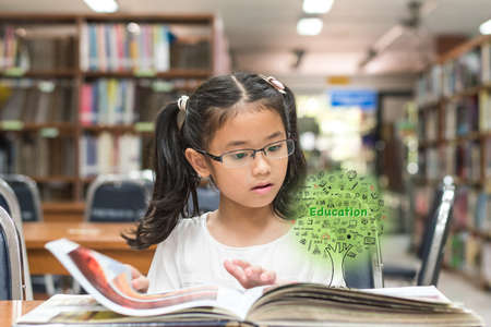 Innovative stem education and tree of knowledge concept with kid reading book in library