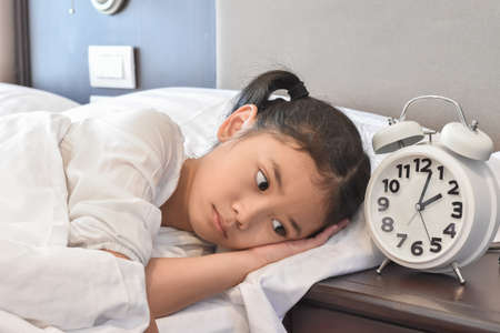 Asian girl child in bed do not sleep suffering insomnia (sleeping disorder) at night in bedroom