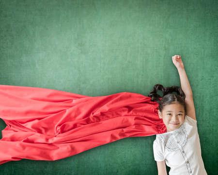 Superhero Asian school girl kid student with inspiration in women rights in education success concept Foto de archivo - 111611263