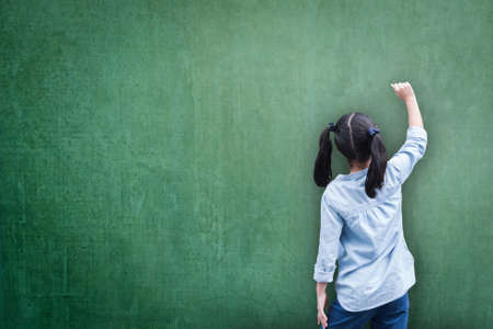 Blank green classroom chalkboard background with student kid back view writing on board