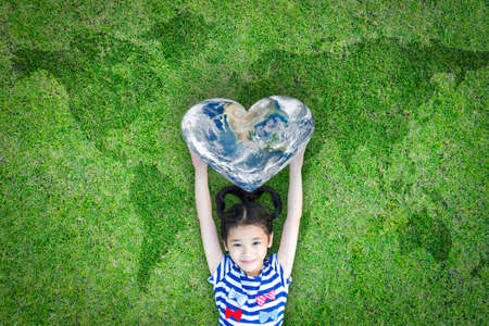 Wereldhartdagconcept en welzijnsgezondheidszorgcampagne met lachende gelukkige jongen op milieuvriendelijk groen gazon.