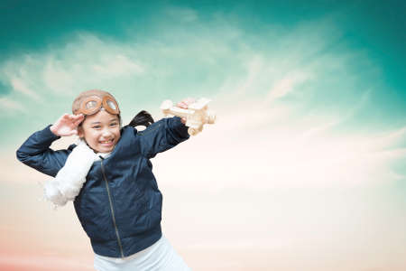 Imagination, inspiration and creative learning motivation education concept with school girl child in pilot costume having fun dreaming high playing flying plane toy over blue sky background