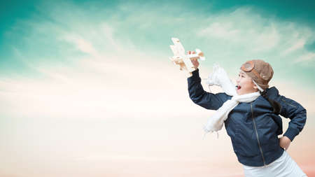 Girl child in pilot costume having fun with creative learning motivation, imagination and inspiration dream high playing flying plane toy over blue sky background