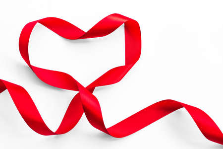 Red satin ribbon bow in heart shape isolated on white background (clipping path), symbolic concept for National heart month Stock Photo