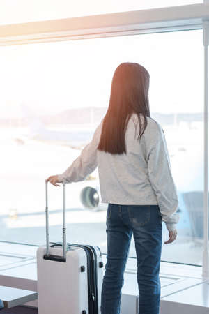 Airport traveller lifestyle of young girl passenger with luggage in airport terminal departure hall area looking out toward airplane checking for flight boarding time and delay status at gate Stockfoto