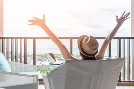 Equilibrio della vita e concetto di vacanza estiva con donna felice che si prende una pausa, celebra il lavoro di successo svolto, riposa casualmente nel posto di lavoro di un hotel resort di lusso con computer pc portatile sulla scrivania