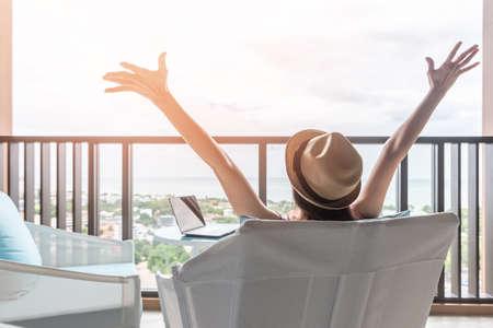 Life-Balance- und Sommerferien-Urlaubskonzept mit glücklicher Frau, die eine Pause macht, erfolgreiche Arbeit feiert, sich entspannt am Arbeitsplatz eines Luxusresorthotels mit Computer-PC-Laptop auf dem Schreibtisch ausruht
