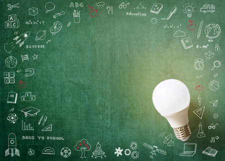 Innovative creative idea concept with LED lightbulb and school doodle on green school's teacher or business chalkboard background with copy space Stok Fotoğraf
