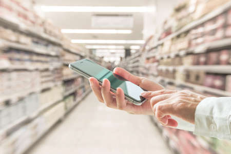 Digital lifestyle business person or shopper using mobile smart phone for retail shopping in supermarket