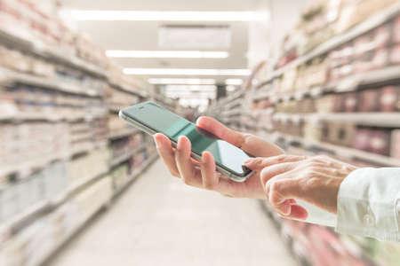 Persona de negocios o comprador de estilo de vida digital mediante teléfono móvil inteligente para compras minoristas en el supermercado