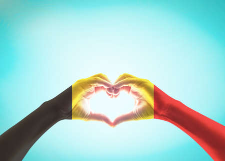 Belgian flag pattern on people heart shape hands (clipping path) on vintage background 版權商用圖片