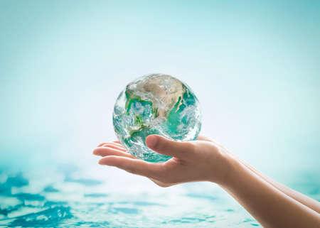 Wereldoceaandag, waterbesparingscampagne, duurzaam ecologisch ecosysteemconcept met groene aarde op de handen van de vrouw op blauwe zeeachtergrond