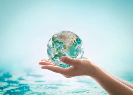 World ocean day, saving water campaign, sustainable ecological ecosystems concept with green earth on woman's hands on blue sea background