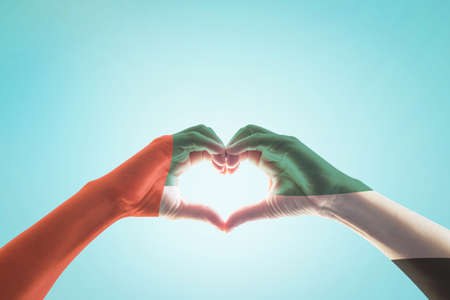 UAE, United Arab Emirate national flag pattern on people's hands in heart shape on blue mint sky background 스톡 콘텐츠