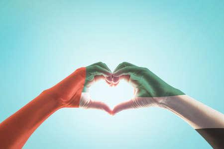 Modello di bandiera nazionale degli Emirati Arabi Uniti e degli Emirati Arabi Uniti sulle mani delle persone a forma di cuore su sfondo blu del cielo di menta