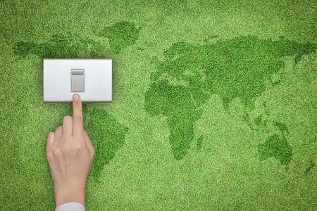 Concepto ecológico y de ahorro de energía con el interruptor de apagado de la mano en el césped de hierba verde con el mapa del mundo