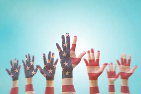 American flag pattern on peoples hand group raising up group
